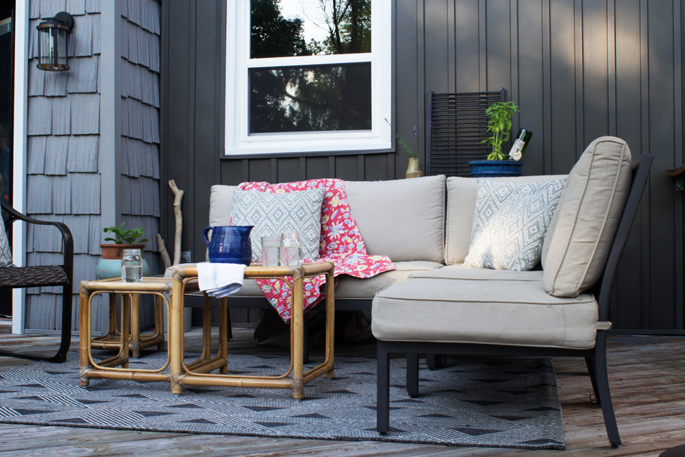 back porch, deck, with neutral sectional and vintage bamboo tables