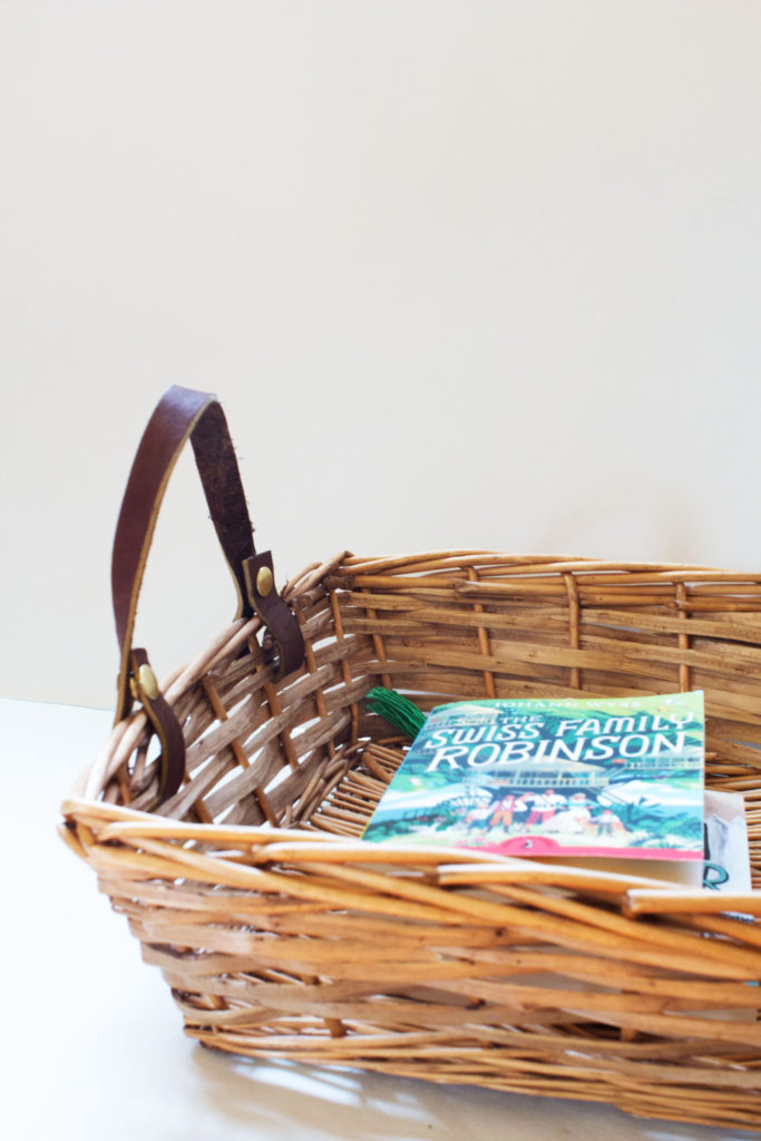 wicker basket with leather handles filled with library books