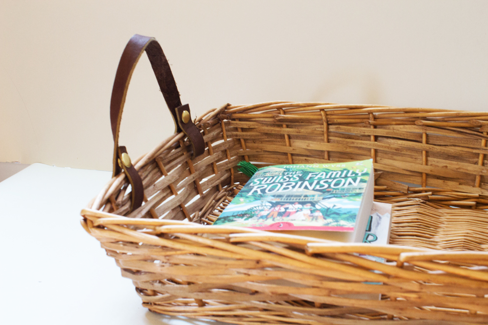 wicker basket with leather handles holding library books