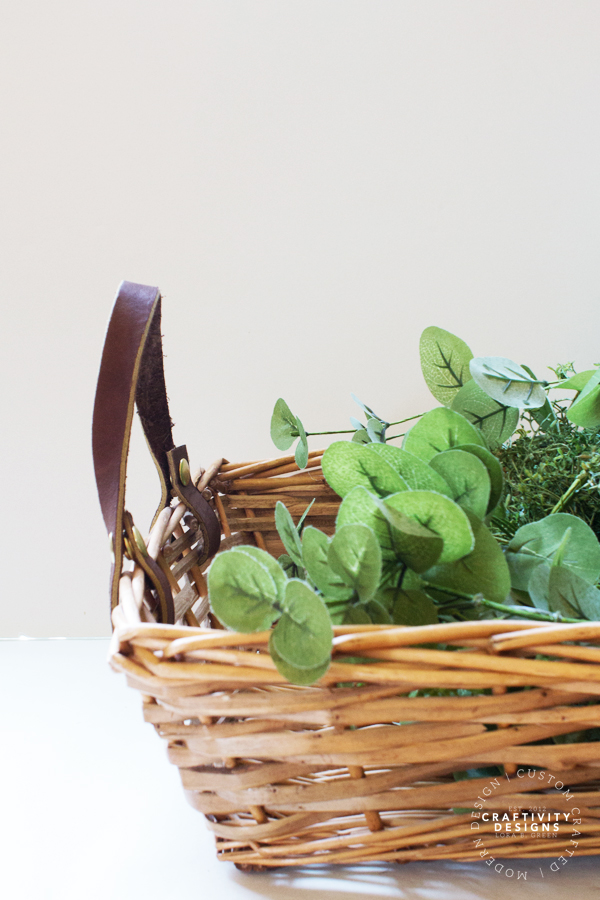 leather handles on a wicker basket filled with greenery