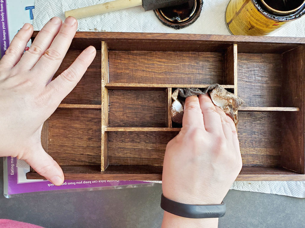 Wipe away wood stain with paper towel to finish the DIY essential oil shelf