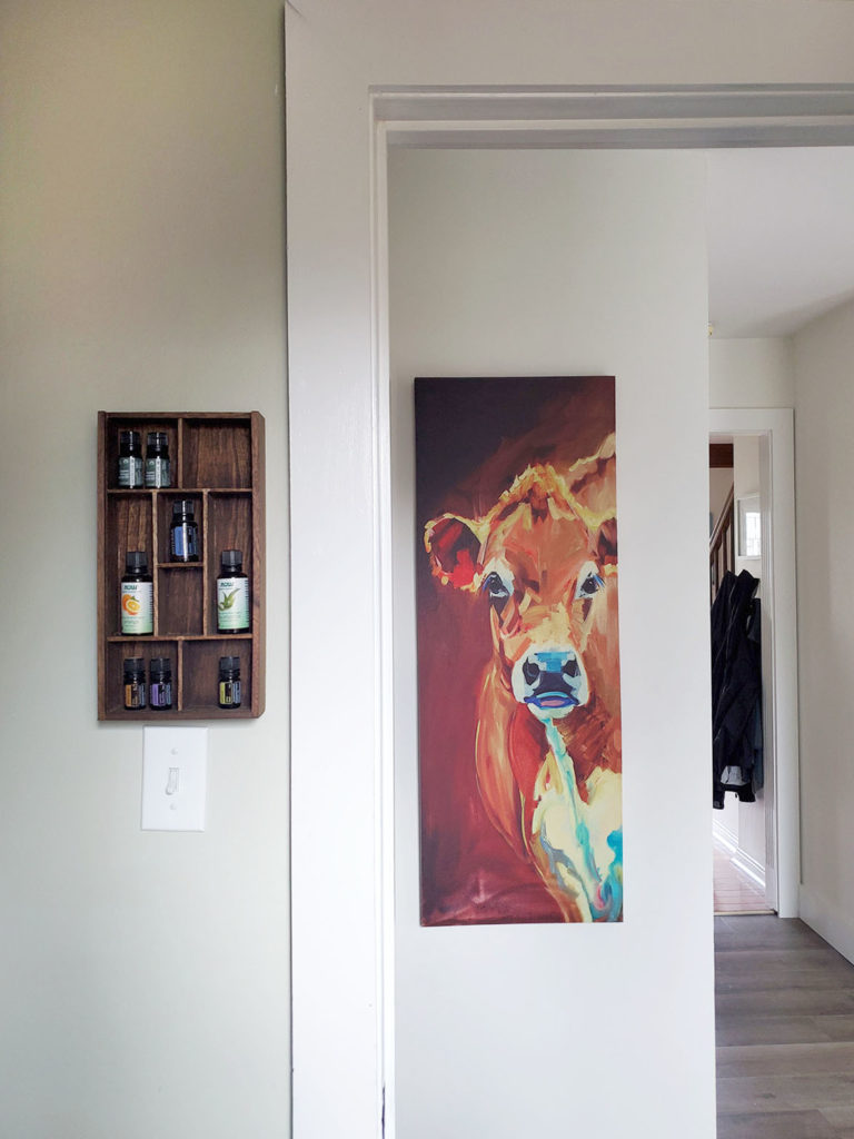 Wooden DIY essential oil shelf hanging on the wall in a laundry room. Cow artwork in hallway.