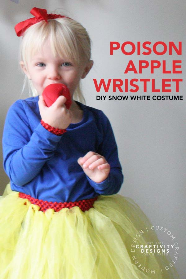 Child dressed for Halloween in a DIY Snow White Costume with a Poison Apple costume prop