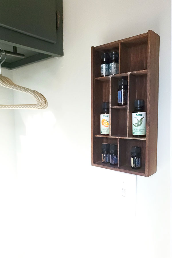 Wooden DIY essential oil shelf hanging on the wall in a laundry room.