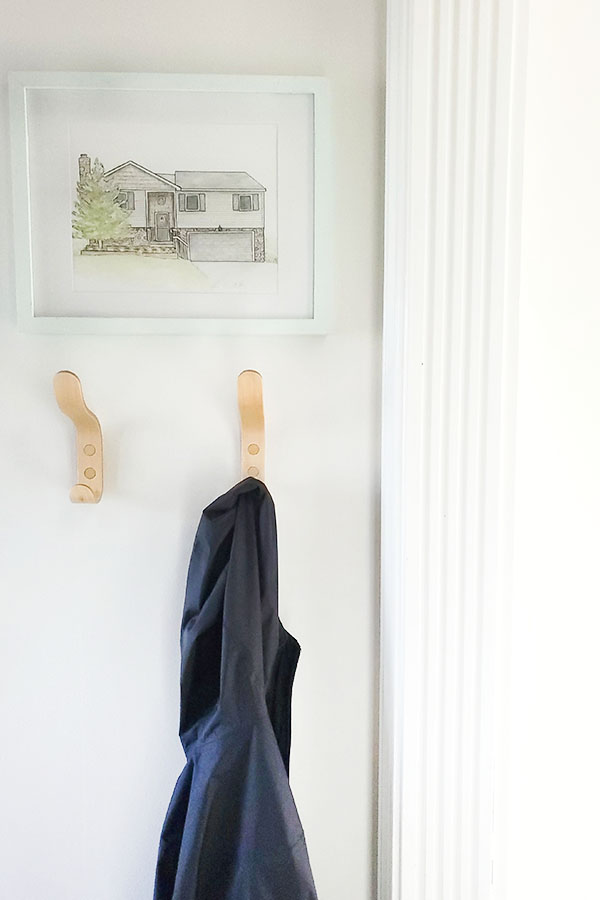 Entryway with modern maple coat hooks and watercolor house painting