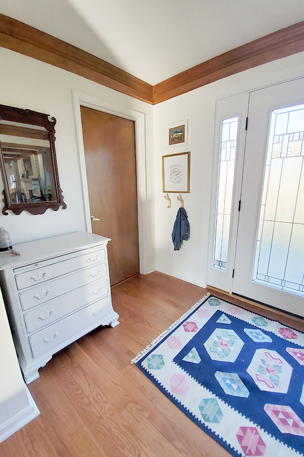 Eclectic entryway with modern coat hooks, wool Romanian rug, antique mirror, and refinished dresser
