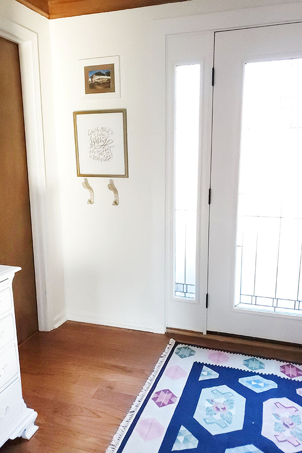 Eclectic entryway with modern coat hooks and wool Romanian rug