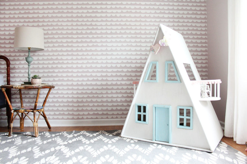 A Pink Girls Bedroom with rattan night stand, dollhouse, and gray rug by Craftivity Designs