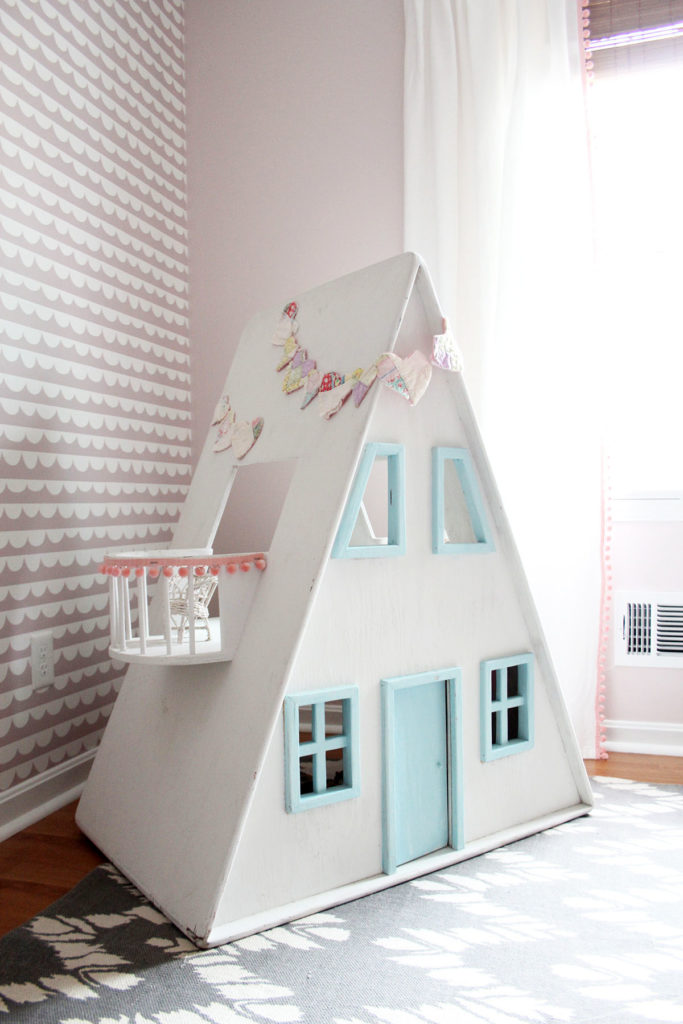 White and aqua wood dollhouse in front of pink wallpaper in a little girls bedroom - by Craftivity Designs