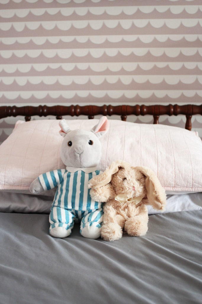Two stuffed animals on a jenny lind bed with pink and white wallpaper in the background.