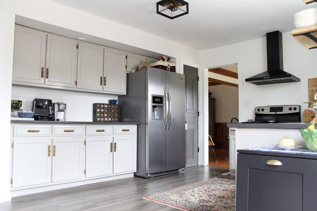 Budget kitchen remodel with gray painted cabinets and black range hood