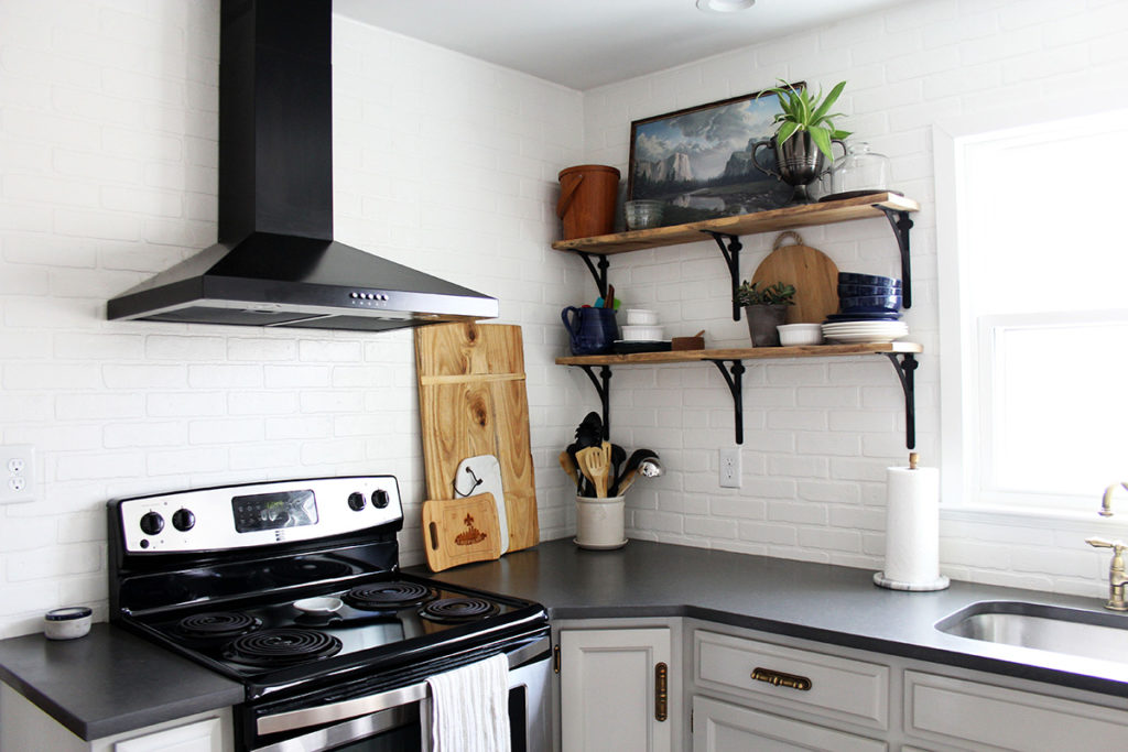 Budget kitchen remodel with gray painted cabinets, reclaimed wood shelves, and black range hood