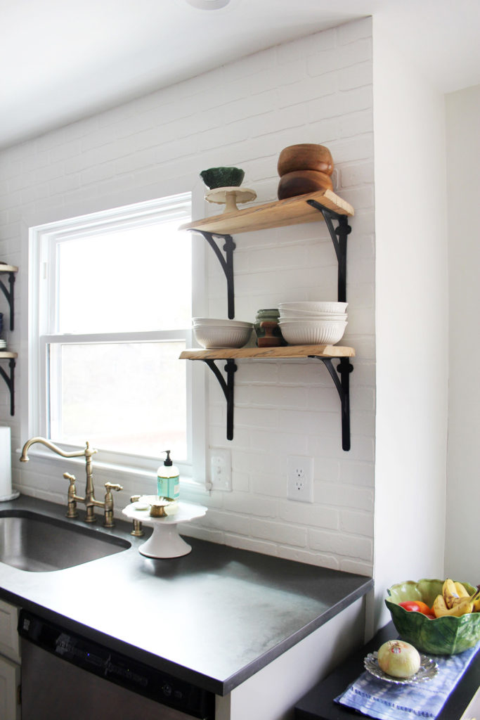 Budget kitchen remodel with reclaimed wood shelves and a brick backsplash