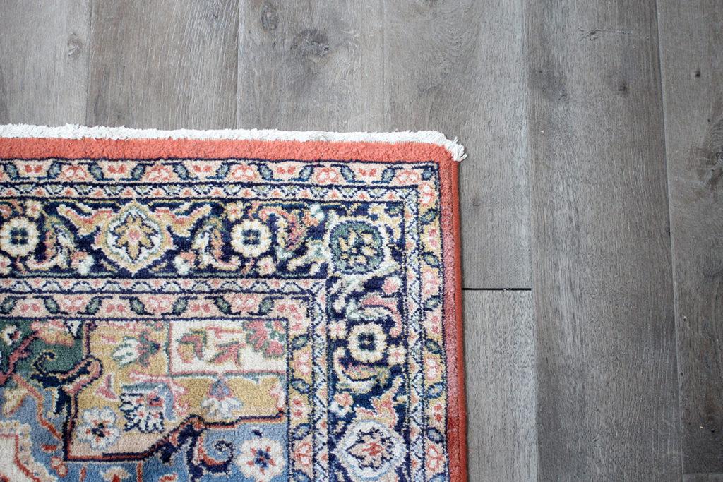 Vintage rug on gray vinyl plank floor