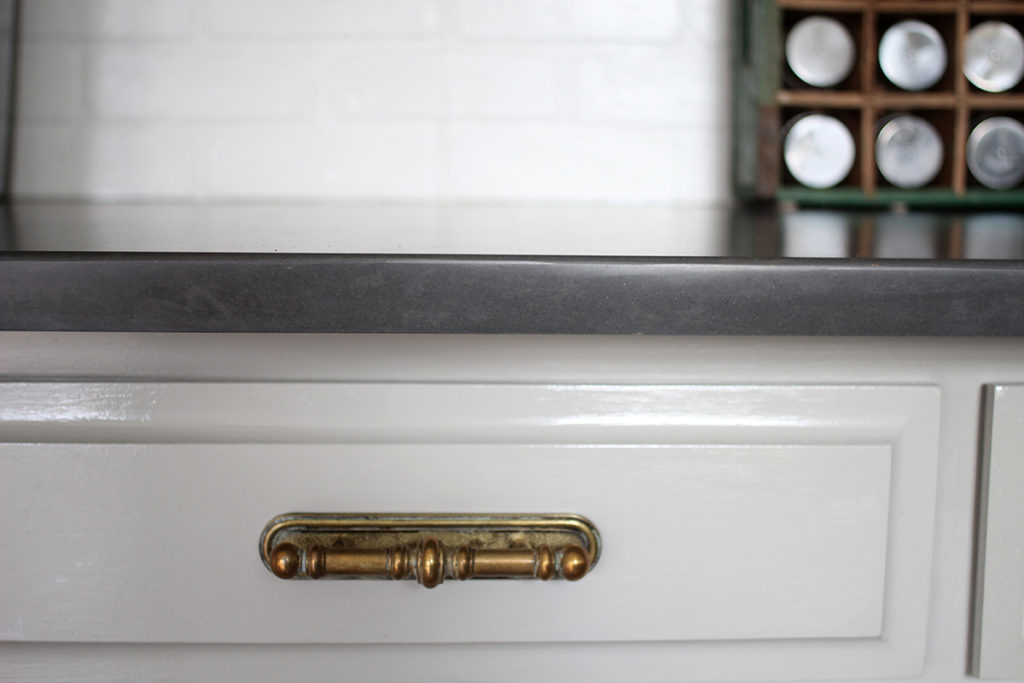 Kitchen Cabinets painted Mindful Gray with Black Quartz Counters and Antique Brass Hardware