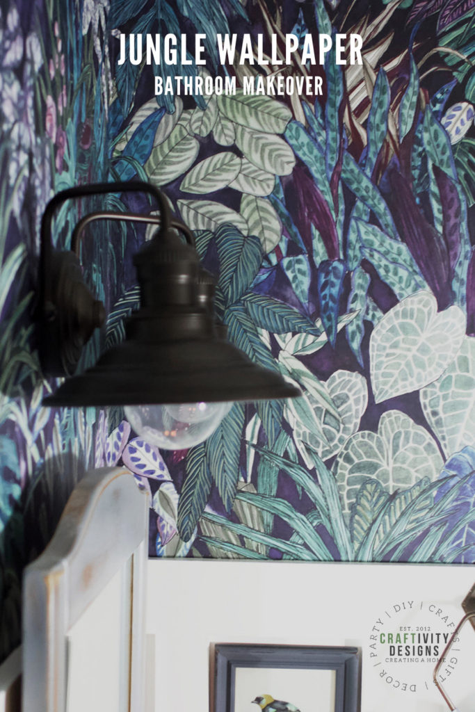 Jungle Wallpaper Bathroom Makeover with Black Wall Sconces, Gray Mirror, and Board and Batten Trimwork