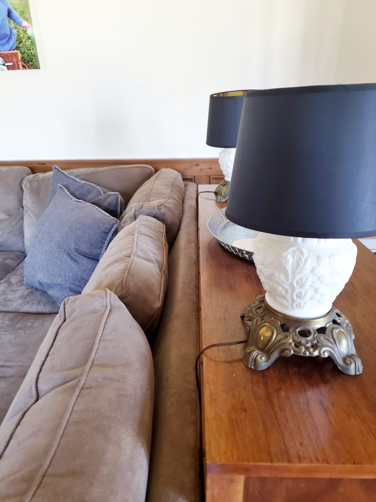 Antique Milk Glass Lamps with Modern Black Lampshades on a Sofa Table
