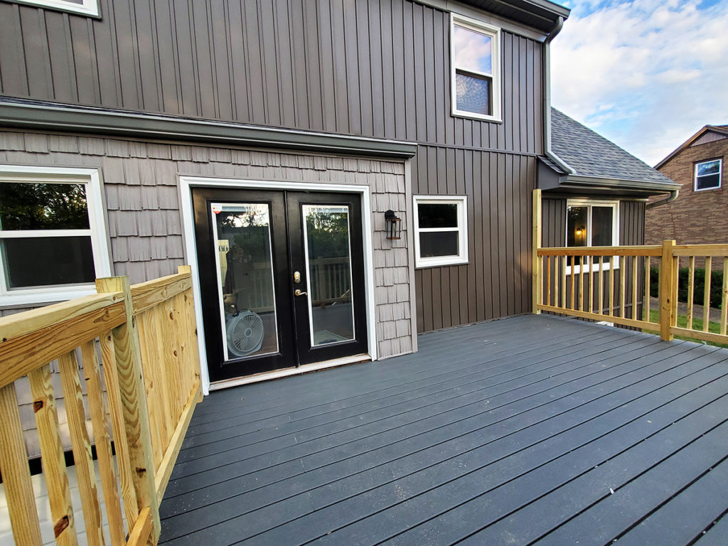 Modern cottage home exterior with board and batten siding, composite decking, and mounting posts for a shade sail
