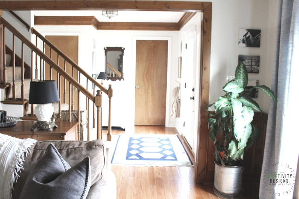Living Room and Entryway with Wood Trimwork, SW Alabaster Walls, Antique Milk Glass Lamps and an Antique Mirror