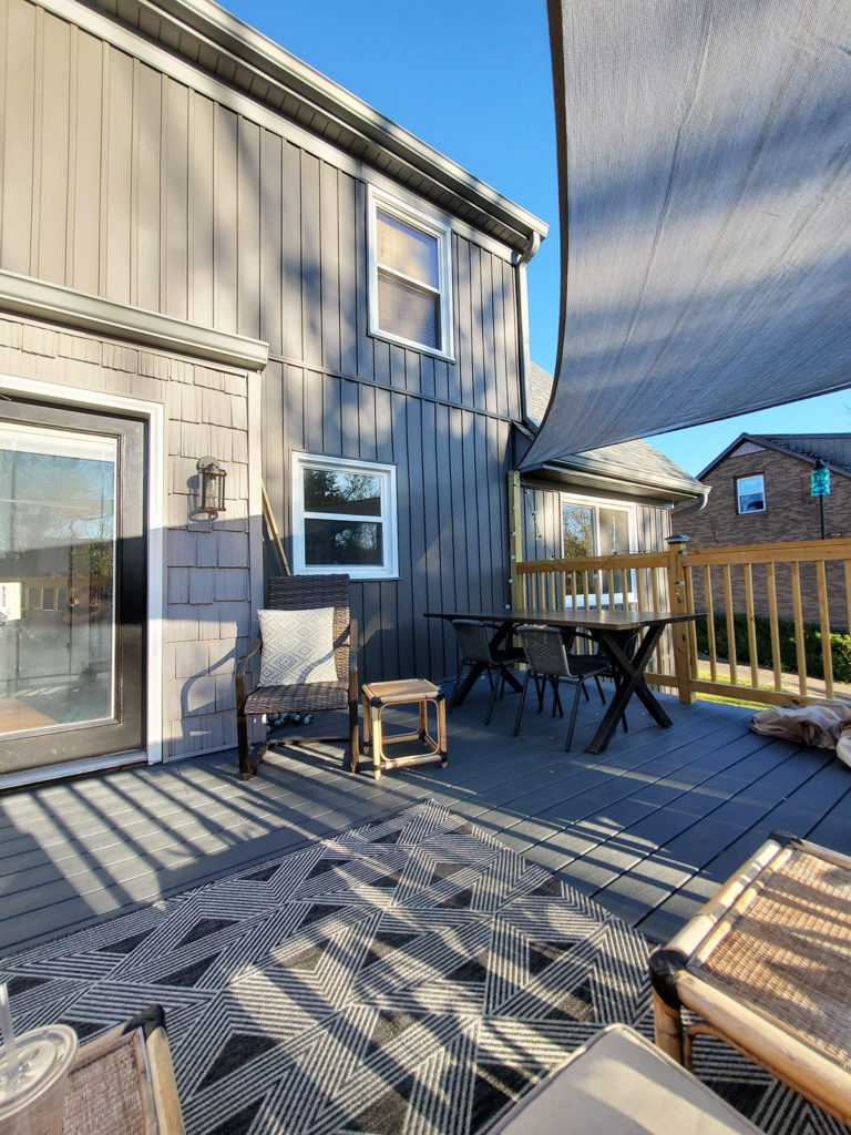 exterior renovation with vertical siding and shade sail