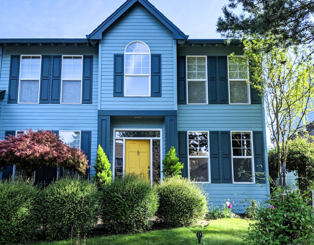 Yellow Front Door on Blue House with Lush Landscaping